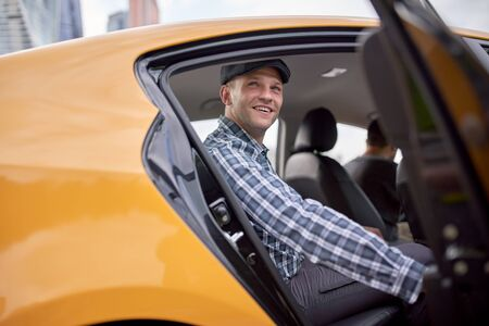 Image of young man in cap and plaid shirt sitting in back seat in yellow taxi Stock Photo