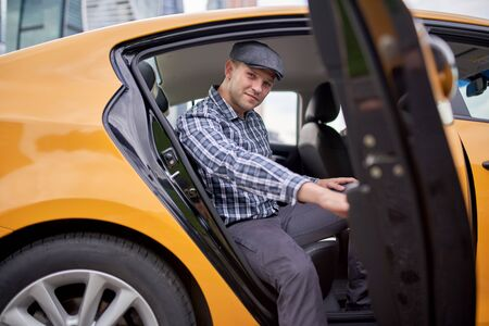 Photo of happy man in cap and plaid shirt looking to camera sitting in back seat in yellow taxi Stock Photo