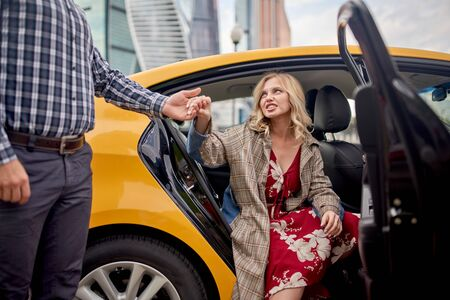 Photo of man giving hand to blonde in long dress sitting in taxi