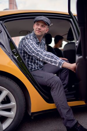 Image of young man in cap and plaid shirt looking to side sitting in back seat in yellow taxi