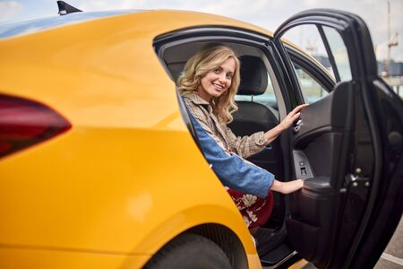 Photo of happy blonde sitting in back seat of yellow taxi with open door