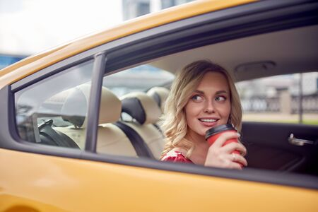 Image of curly blonde with glass of coffee in her hands sitting in back seat of yellow taxi