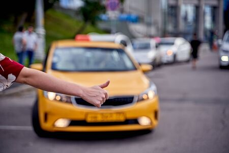 Image from back of woman with outstretched hand stopping taxi in afternoon on blurred background. Stock Photo