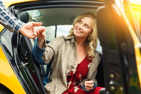 Photo of man giving hand to blonde woman sitting in back seat of taxi on summer day