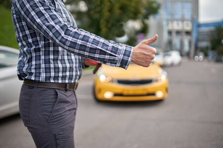 Picture of man with outstretched hand stopping taxi in afternoon on blurred background.