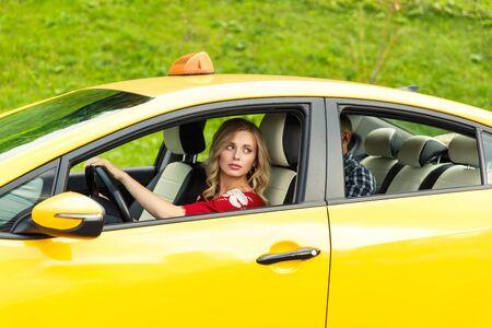 Foto van blonde vrouwelijke chauffeur die in de zomer in gele taxi zit