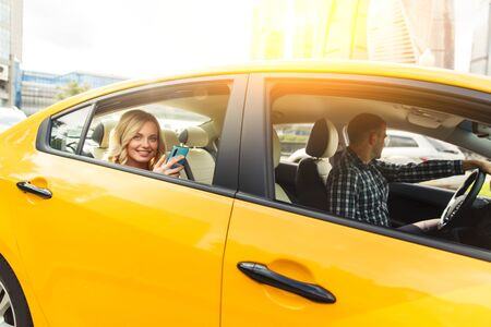 Photo of young blonde with phone in her hand sitting in back seat of yellow taxi with driver.