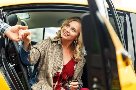 Photo of man giving hand to blonde woman sitting in back seat of taxi