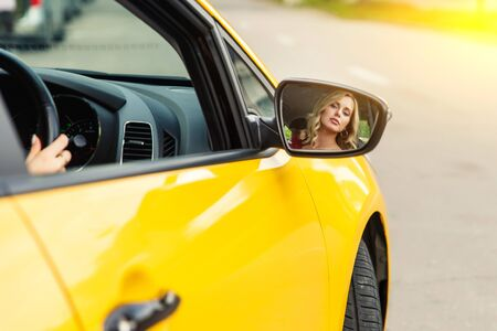 Photo of female driver reflecting back in yellow taxi mirror.