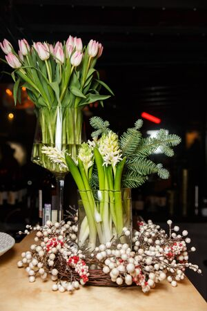 Table with bouquet of tulips, branches of spruce, white berries.