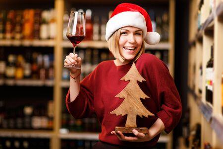 Foto van gelukkige vrouw in kerstmuts met glas en houten boom in handen van winkel