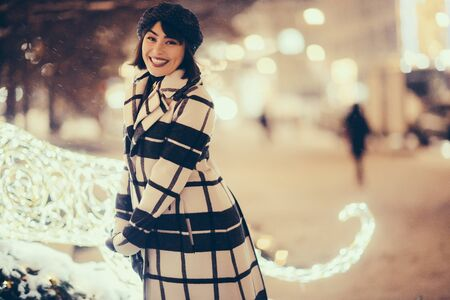 Smiling woman in checkered coat and black hat on evening walk on blurred background 写真素材