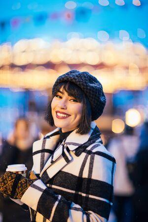 Image of happy brunette with glass in hands on walk on street Banco de Imagens