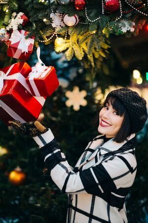 Photo of happy woman looking into camera while standing next to decorated Christmas tree Banco de Imagens
