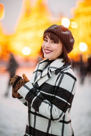 Image of young brunette in hat and checkered coat on winter walk. Banco de Imagens
