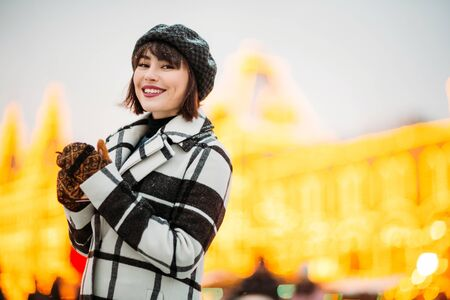 Photo of smiling brunette in hat and checkered coat on winter walk. Banco de Imagens - 135017885