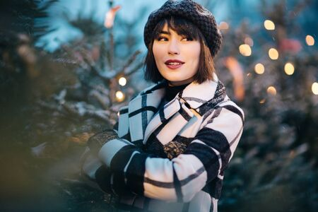 Photo of young brunette next to branches of spruce with garland in evening Banco de Imagens - 135017886