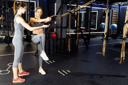 Coach and sportive woman with arms raised train with elastic bands