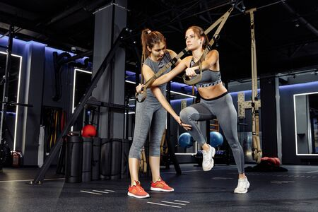 Coach and athlete woman with arms raised train with elastic bands