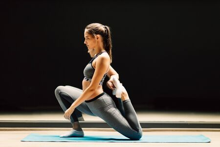 Sporty woman stretching sitting on rug in sports hall
