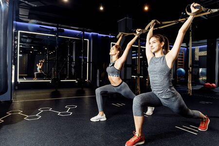 Two athletes with arms raised train with elastic bands
