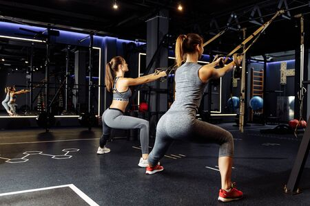 Two athletes with arms raised train with elastic bands in gym Stok Fotoğraf