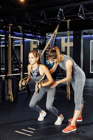 Two young sportswomen exercising with rubber bands in stretch
