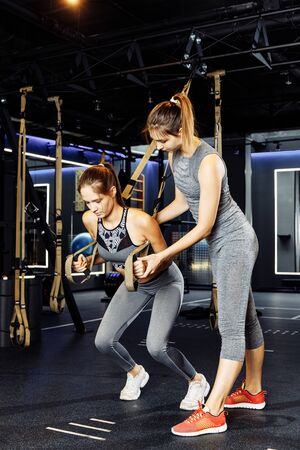 Two young athlete women exercising with rubber bands in stretch