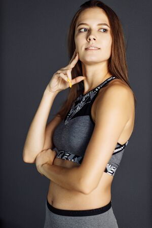 Pensive sports girl on empty gray background
