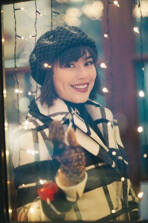Happy girl in plaid coat . Christmas garland in evening. Banco de Imagens - 135017891