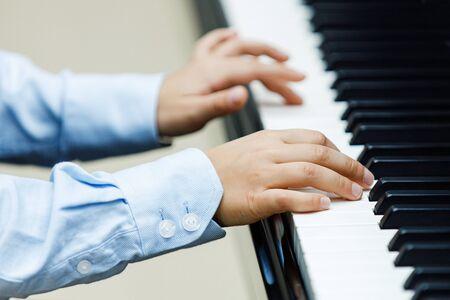 Small boy plays piano, close up Banco de Imagens