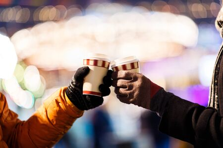 Photo of peoples hands with glasses on street in winter