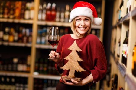 Image of happy blonde in Santa hat with glass and wooden tree in hands of store