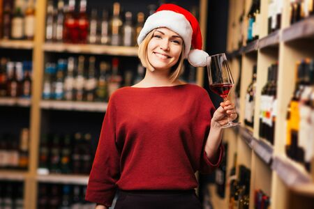 Picture of happy girl in Santa hat with glass in hands of store Banco de Imagens