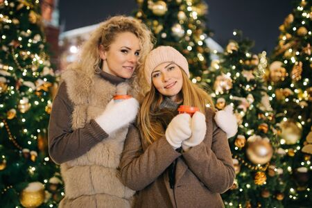 Photo of two women with glasses on winter walk on background of decorated spruce