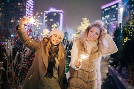 Image of two women with Bengal lights on winter walk on background of decorated spruce