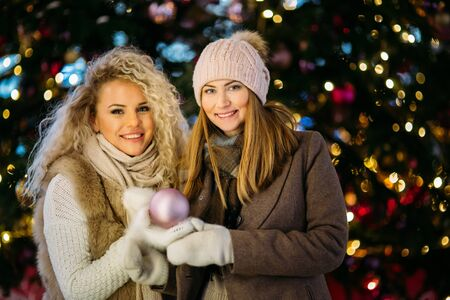 Image of two women on winter walk on background of decorated spruce