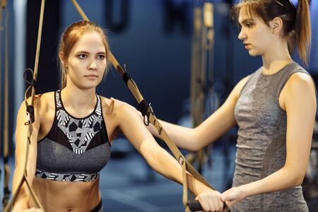 Sportswoman with trainer on arm muscle training