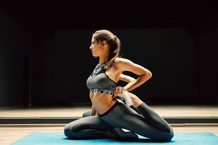 Woman stretching sitting on rug in sports hall