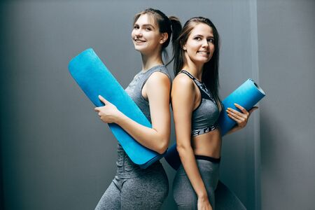 Two happy athlete women with blue rug on background of gray wall