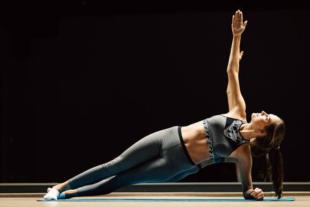 Woman on stretch in plank pose on rug in sports hall on black background Banco de Imagens