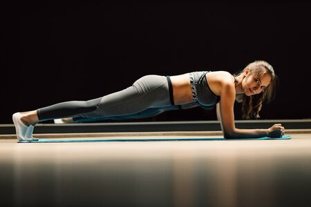 Sportswoman on stretch in plank pose on rug in sports hall Banco de Imagens