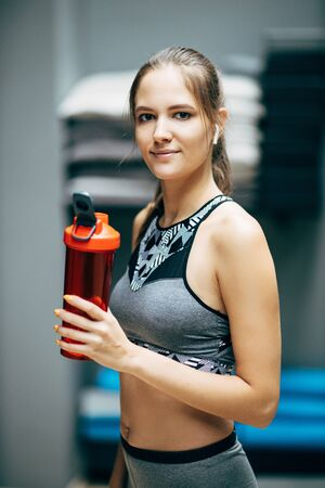 Sporty woman with red bottle of water on blurry background