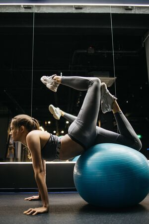 Young sportswoman lying on fitball stretching in gym Banco de Imagens