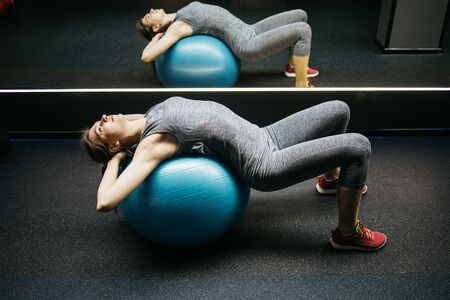 Young sportswoman lying on fitball is doing fitness in gym