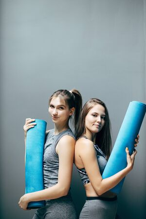 Two sporty women with blue rug on background of gray wall