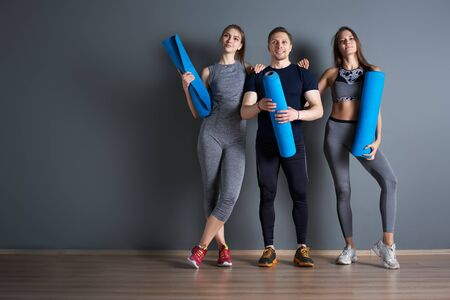 Two athletic women and man with twisted blue rugs against gray empty wall
