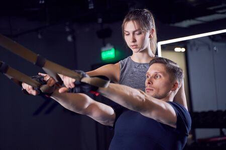 Athletic male in training with elastic bands and girl trainer