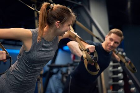 Sportsman and woman in training with elastic bands