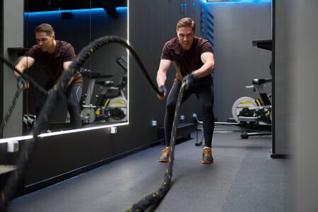 Athlete man in training with ropes near mirror.